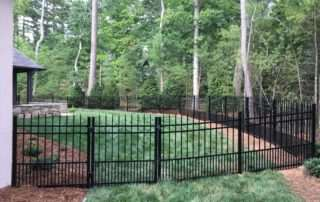 aluminum and iron fencing on grass and mulch