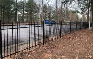 iron fencing bordering parking lot