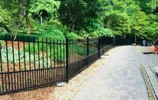 iron fence along brick walkway with river rock border