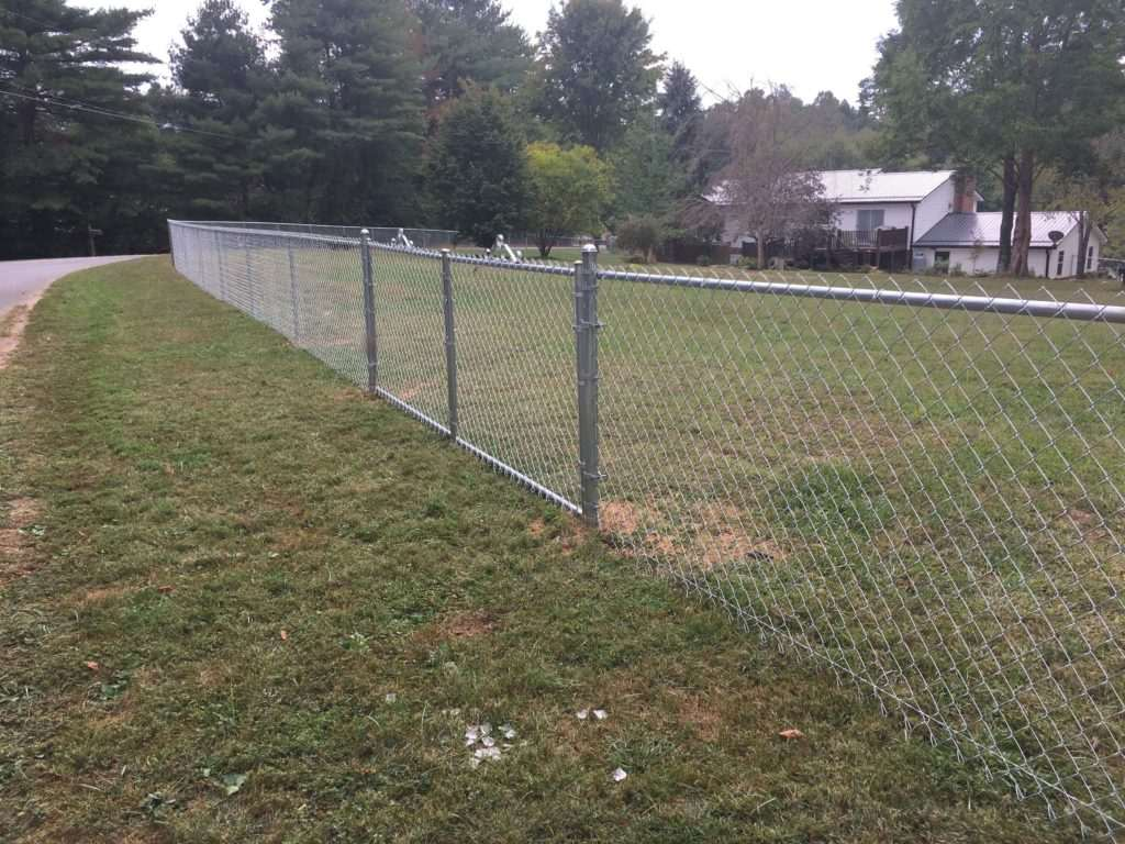 chain link fence with gate surrounding home