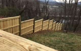 Wooden step-down fence on downward slope