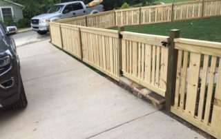 Wood fence with swing gate lining driveway