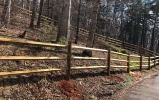 Wooden split rail fence on a wooded hill next to paved road