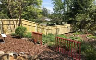 Garden surrounded by wood fence with a slope