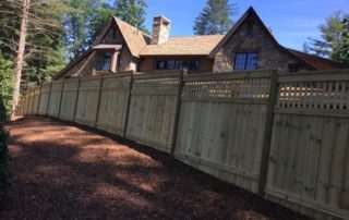 Wooden privacy fence around large stone house