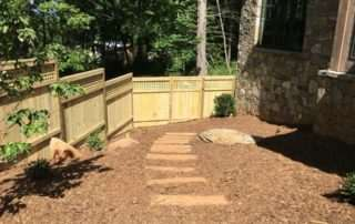 Wood fence bordering stone pathway in mulch