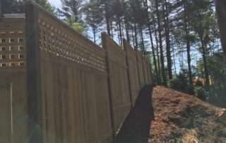 Wooden fence on sloping upward hill on mulch