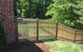 Wooden fence going down sloping backyard with trees