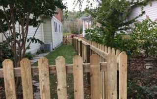 Wooden picket fence between two houses