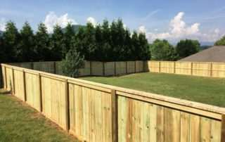 large wooden fence bordering backyard