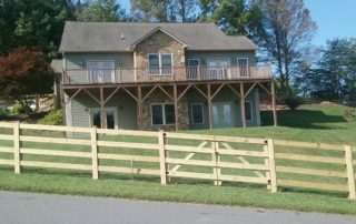 Split rail wooden fence around house on hill
