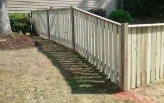 partial side yard wooden fence on uneven ground