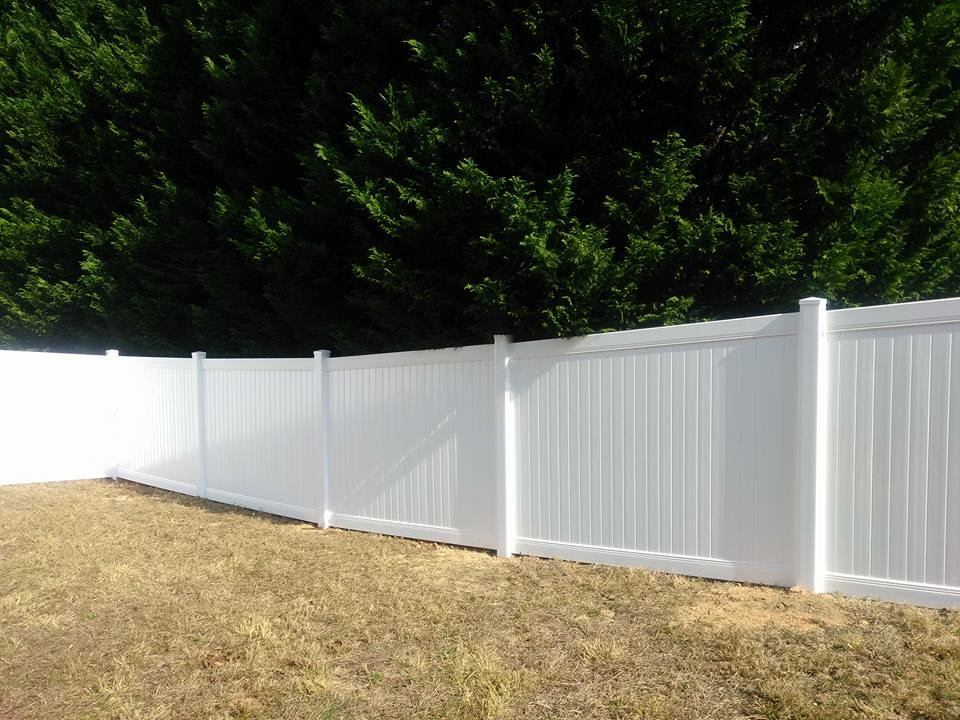 White PVC and vinyl fencing on uneven ground.