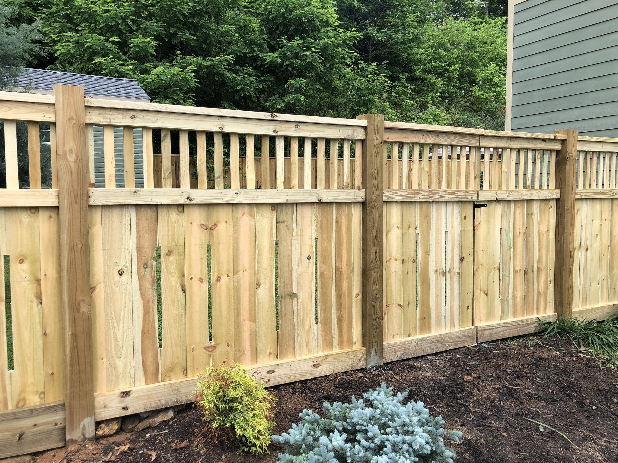 Residential wooden fence on mulch
